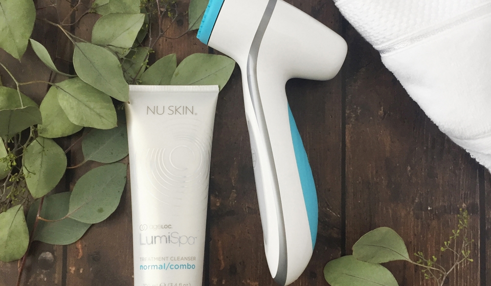 LumiSpa device and Cleanser  with a luxurious towel on a wood surface with some leafy branches.